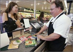In this Aug. 25, 2008 file photo, Kris Loew, left, talks with a grocery clerk as she checks out at a market in Palo Alto, Calif. Consumers are less likely to see prices drop at the checkout line even now that oil prices are plunging. (AP Photo/Paul Sakuma, file)