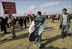A demonstrator carries an image of the modern Turkey's founder Ataturk on his shoulders during a protest in front of the Silivri prison in Silivri, west of Istanbul, Turkey, Monday, Oct. 20, 2008. The trial of 86 people accused of conspiring to overthrow Turkey's Islamic-oriented government began in chaos when defendants and lawyers complained they couldn't hear in the overcrowded courtroom. Those on trial include a retired general, the leader of a small leftist and nationalist party, a newspaper editor, a best-selling author and a former university dean. (AP Photo/Murad Sezer)