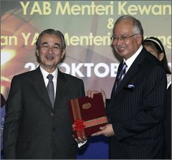 Malaysian Prime Minister Abdullah Ahmad Badawi, left, smiles as he hands over his finance minister's post to his deputy Najib Razak, right, in Putrajaya, Malaysia, Monday, Oct. 20, 2008. Malaysia announced plans Monday to prop up the stock market and lure more foreign investment amid expectations of slower economic growth next year. (AP Photo/Lai Seng Sin)