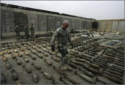 A U.S. soldier of the Explosive Ordinance Disposal (EOD) team walks through munitions at a joint U.S.-Iraqi army base in Sadr City, Baghdad, Iraq, on Tuesday, Oct. 21, 2008. The munitions were seized by the U.S. army and Iraqi security forces during recent operations in the Shiite enclave of Sadr city. (AP Photo/Khalid Mohammed)