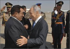 In this photo released by the Israeli Government Press Office, Egyptian President Hosni Mubarak, left, welcomes Israeli President Shimon Peres, center, at Sharm El Sheikh airport, Egypt, Thursday, Oct. 23, 2008. Speaking at a joint press conference with Mubarak Peres has endorsed the &quot;spirit&quot; of an Arab peace initiative, saying it's an &quot;opportunity&quot; that can bring peace to the Middle East.(AP Photo/ GPO, Amos Ben Gershom, HO)