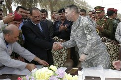 "Maj. Gen. Michael Oates, U.S. commander south of Baghdad, right, shakes hands with Salim al-Musilmawi, Babil's provincial governor,during a transfer ceremony held in the city of Hilla, near the ruins of the ancient city of Babylon, on Thursday, Oct. 23, 2008. The U.S. relinquished control of a southern province that includes Sunni areas once known as the ""triangle of death,"" handing security responsibility to the Iraqi government on Thursday.Babil is the 12th of 18 Iraqi provinces to be placed under Iraqi control and a sign of the improving security. U.S. forces will remain in the area to assist the Iraqis when needed.(AP Photo/Alaa al-Marjani)"