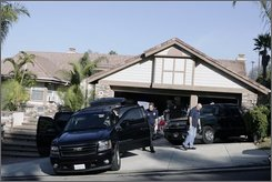 Law enforcement officers investigate the home of Ruben Cavazos, former national president of the Mongols motorcycle gang Tuesday, Oct. 21, 2008, in West Covina, Calif. At least 38 members of the Southern California-based Mongol motorcycle gang were arrested under a federal racketeering indictment that included charges of murder, attempted murder, assault, as well as gun and drug violations, Bureau of Alcohol, Tobacco, Firearms and Explosives spokesman Mike Hoffman said. (AP Photo/Ric Francis)