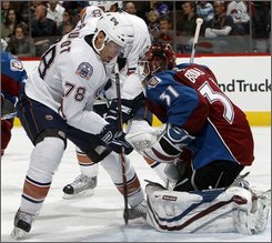 Edmonton Oilers right winger Marc Pouliot, left, has his shot stopped by Colorado Avalanche goalie Peter Budaj, of Slovakia, in the second period of an NHL hockey game in Denver on Thursday, Oct. 23, 2008. (AP Photo/David Zalubowski)