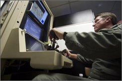 Col. Charles W. Manley, commander of the 163d Maintenance Group,163d Reconnaissance Wing, pilots a training simulator for the U.S. Air Force's MQ-1 Predator, at the March Air Reserve Base in Riverside County, Calif., in this June 25, 2008 file photo. Scrambling to meet commanders' insatiable demands for unmanned aircraft, the Air Force is launched two new training programs Wednesday Oct. 22, 2008, including an experimental one that would churn out up to 1,100 desperately needed pilots to fly the drones over Iraq and Afghanistan. As many as 700 Air Force personnel have expressed some interest in the test program, which will create a new brand of pilot for the drones, which are flown by remote control from a base in Nevada. (AP Photo/Damian Dovarganes, FILE)