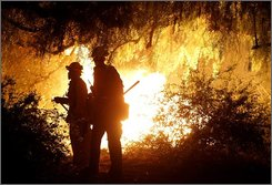 Firefighters watch as a brush fire burns out of control in the Bel Air area of Los Angeles on Thursday, Oct. 23, 2008. Los Angeles fire spokesman Brian Humphrey  says all lanes of the 405 Freeway have been closed through the Sepulveda Pass. (AP Photo/Dan Steinberg)