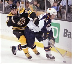 Boston Bruins' Marc Savard, left, battles Atlanta Thrashers' Tobias Enstrom, of Sweden, for the puck in the first period of an NHL hockey game, Saturday, Oct. 25, 2008, in Boston. (AP Photo/Michael Dwyer)