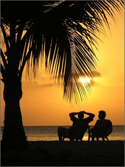 In this Feb. 10, 2006 file photo, tourists relax enjoying the sunset on a beach in the Caribbean city of Cartagena, Colombia. Several carriers have said that advance bookings for the 2008-2009 holiday season, show their planes are expected to be as full as or fuller than a year ago in part because they have taken so many seats out of the air. (AP Photo/Ricardo Maldonado, file)