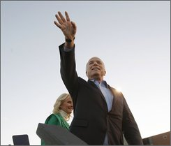 Republican presidential candidate Sen. John McCain, R-Ariz., waves to supporters as he takes the stage with his wife Cindy during a campaign rally at Durango High School in Durango, Colo., Friday evening, Oct. 24, 2008. (AP Photo/Stephan Savoia)
