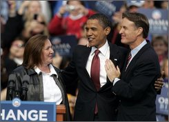 Democratic presidential candidate Sen. Barack Obama, D-Ill., center, hugs Sen. Evan Bayh, D-Ind., right, and Andrea Mooney of Pendleton, Ind. after Mooney introduced Obama at a rally on the American Legion Mall in Indianapolis, Thursday, Oct. 23, 2008.  (AP Photo/Michael Conroy)