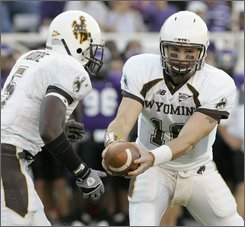 Wyoming quarterback Karsten Sween (16) gets set to hand the football to running back Devin Moore (5) in their game against TCU in the first half of their NCAA college football game in Fort Worth, Texas, Saturday, Oct. 25, 2008. (AP Photo/Donna McWilliam)