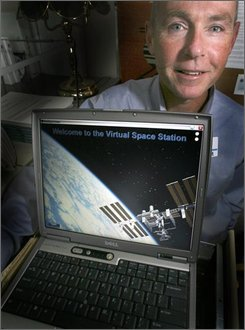 "Dartmouth psychologist Dr. Mark Hegel poses in his office with his laptop in Lebanon, N.H., Friday, Oct. 17, 2008. Hegel is working on a computer program, ""The Virtual Space Station,"" that will guide astronauts through treatment for depression and other problems while in space. (AP Photo/Jim Cole)"