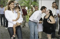 Mayoral candidate Eduardo Paes, of the Brazilian Democratic Movement Party, greets a supporter at right, as his wife and daughter walk at left, after casting his ballot during municipal elections in Rio de Janeiro, Brazil, Sunday, Oct. 26, 2008. (AP Photo/Ricardo Moraes)