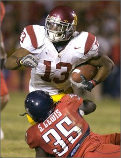 Southern California's Stafon Johnson (13) is stopped by Arizona's Sterling Lewis (35) during the second half of an NCAA college football game at Arizona Stadium in Tucson, Ariz., Saturday, Oct. 25, 2008. Southern California won 17-10. (AP Photo/John Miller)