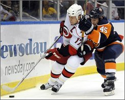 Carolina Hurricanes' Rod Brind'Amour moves the puck past New York Islanders' Nate Thompson (45) during the first period of their NHL hockey game at the Nassau Coliseum in Uniondale, N.Y., Saturday, Oct. 25, 2008. (AP Photo/Ed Betz)