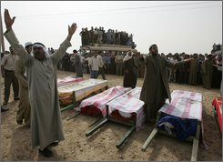 """Syrian villagers shout anti-U.S. slogans as they gather near the coffins of relatives who died a day before when U.S. military helicopters launched an extremely rare attack on Syrian territory during their funeral procession in the Sukkariyeh Farm near the town of Abu Kamal, an area of farms and brick factories about five miles (eight kilometers) inside the Syrian border, on Monday, Oct. 27, 2008. Four U.S. military helicopters flying along the Euphrates River struck an area along Syria's border with Iraq Sunday, killing eight people, the Syrian government said, condemning what it called """"serious aggression."""" (AP Photo/Hussein Malla)"""