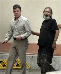 Colombia's Defense Minister Juan Manuel Santos, left, walks along with former hostage Oscar Tulio Lizcano at a military base in Cali, Colombia, Sunday, Oct. 26, 2008. Lizcano, a 62-year-old lawmaker who was held captive eight years by rebels of the Revolutionary Armed Forces of Colombia, or FARC, walked to freedom in a western Colombia jungle on Sunday along with the young guerrilla commander who had been his jailer. (AP Photo/Christian Escobar Mora)