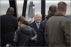 Republican presidential candidate Sen. John McCain, R-Ariz. steps off his campaign bus on the tarmac in bad weather before boarding his campaign plane in Middletown, Pa., Tuesday, Oct. 28, 2008. (AP Photo/Carolyn Kaster)
