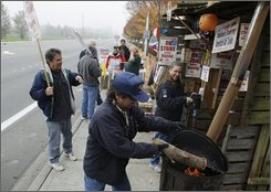 Striking Boeing Co. worker Kevin Riley adds wood to a burn barrel while Anne Scholzen holds a pot of chili at upper right as they serve strike duty Tuesday, Oct. 28, 2008, in front of the headquarters for Boeing's Commercial Airplanes division in Renton, Wash. Members of the Machinists union, who have been on strike since Sept. 6, 2008, are scheduled to vote Saturday on a new contract offer from Boeing. (AP Photo/Ted S. Warren)