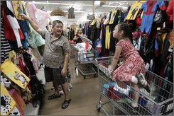 Tan Du, left, and his daughter Kelly, 4, shop for a Halloween custom at a Wal-Mart Supercenter Thursday, Oct. 2, 2008, in Rosemead, Calif. Investors will be looking for details about how Wal-Mart Stores Inc. will navigate through a consumer spending slump that's feared to be deep and long-lasting at its two-day investors' meeting, starting Monday, Oct. 27, 2008. (AP Photo/Ric Francis)