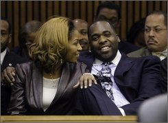Former Detroit Mayor Kwame Kilpatrick, right, smiles with his wife Carlita waiting for his sentencing hearing in Detroit, Tuesday, Oct. 28, 2008. The four-month sentence is part of an agreement worked out with prosecutors when Kilpatrick, a Democrat, pleaded guilty to obstruction of justice on Sept. 4 for lying about an affair with his chief of staff. A separate but identical punishment for assaulting a sheriff's detective will run at the same time.   (AP Photo/Paul Sancya)