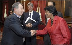 In this photo released by the Presidency of Colombia, Colombia's President Alvaro Uribe, left, shakes hands with United Nations High Commissioner for Human Rights Navanethem Pillay during a meeting at the presidential palace in Bogota, Monday, Oct. 27, 2008. (AP Photo/Presidency of Colombia,Miguel Angel Solano)