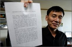 Former North Korean prisoner Jung Gyoung Il, who spent three years in Camp No. 15 in Yodok, northeast of Pyongyang, on charges of spying for South Korea, shows a letter which he wrote for prisoners in North Korea during an interview with the Associated Press in Seoul, South Korea, Monday, Oct. 29, 2008.  (AP Photo/ Lee Jin-man)