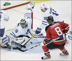 New Jersey Devils' Dainius Zubrus (8) scores past Toronto Maple Leafs goalie Vesa Toskala (35) as Toronto's Tomas Kaberle (15) attempts to help defend during the first period of an NHL hockey game at Prudential Center in Newark, N.J. Wednesday, Oct. 29, 2008. (AP Photo/Rich Schultz)