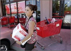 In this July 29, 2008 file photo, a customer walks out with paper purchased from an Office Depot store in Mountain View, Calif. Office Depot said Wednesday, Oct. 29, 2008, weakness in Florida and other parts of North America, and store-closing costs led it to loss in the third quarter. (AP Photo/Paul Sakuma, file)