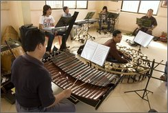 In this Jan. 17, 2007 file photo, Cambodian musicians play Western and traditional Cambodian instruments music for an opera at a rehearsal room in Phnom Penh, Cambodia.  Cambodia's first rock opera will make its world premiere in Phnom Penh next month, a cultural milestone in the Southeast Asian country where performing arts were banned during the brutal Khmer Rouge years.  Organizers said Wednesday, Oct. 29, 2008,  the show will open a 10-day run Nov. 28 in a converted movie theater in the capital, Phnom Penh, a year later than its planned debut at the end of 2007. (AP Photo/Heng Sinith, FILE)