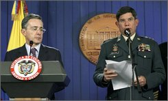 Colombia's Armed Forces Chief Gen. Freddy Padilla, right, reads the names of fired soldiers during a news conference as Colombia's President Alvaro Uribe looks on at the presidential palace in Bogota, Wednesday, Oct. 29, 2008. Uribe's government fired 25 soldiers, including three generals and four colonels, over the killings of at least 11 civilians who disappeared from a Bogota suburb and were found dead hundreds of miles away. (AP Photo/William Fernando Martinez)