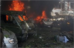 An injured person lies as vehicles burn near a blast site in Gauhati, India, Thursday, Oct. 30, 2008. At least 13 blasts ripped through cities across India's northeastern state of Assam on Thursday, killing at least 30 people and wounding dozens more, police and witnesses said. (AP Photo/Anupam Nath)