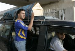 A coffin with one of the three fatal victims of a roadside bomb, is seen on the top of a van, as a relative waves, in Baghdad, Iraq, on Thursday, Oct. 30, 2008.  A roadside bomb exploded, Wednesday night, in Palestine Street eastern Baghdad, targeting a police patrol, killing 3 civilians and injuring 14 others,the police said. (AP Photo/Karim Kadim)