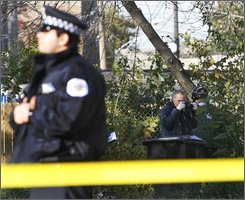 A Chicago Police Department photographer takes pictures on the city's West Side, Wednesday, Oct. 29, 2008, where they were gathering evidence near the site where 7-year-old Julian King, nephew of singer and Oscar winner Jennifer Hudson, was found shot to death in an SUV on Monday. (AP Photo/Nam Y. Huh)