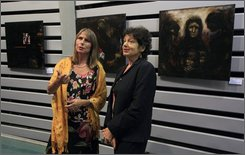 """Bettina Goering, whose great-uncle was was the infamous Nazi leader Hermann Goering, left, and artist Ruth Rich, an Australian artist whose brother was murdered by the Nazis and whose parents survived the Holocaust, right, stand next to Rich's paintings in the Israeli city of Ashkelon, Sunday Oct. 26, 2008. Goering and Rich came to Israel for the screening of """"Bloodlines"""", a documentary recording their emotional encounters. Goering said it was only thanks to her meetings with Rich, where she faced an angry victim, that she was able to finally breakthrough from a guilt-ridden life, filled of psychological and physical breakdowns.(AP Photo/Tsafrir Abayov)"""