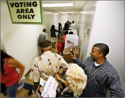 Clerk Brian Spears directs voters to booths as hundreds cast their general election ballots a week early at the Los Angeles County Registrar-Recorder's office in Norwalk, Calif., Tuesday, Oct. 28, 2008. (AP Photo/Reed Saxon)