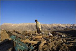 A Pakistani man walks through the debris of his house destroyed by an earthquake in Ziarat, about 130 kilometers (81 miles) south of Quetta, Pakistan, on Friday, Oct. 31, 2008. A 6.4-magnitude earthquake struck an impoverished region of Pakistan's Baluchistan province before dawn on Wednesday, demolishing some 3,000 houses. A Pakistani official says the death toll from the earthquake in southwestern Pakistan will likely rise to more than 300. (AP Photo/Emilio Morenatti)