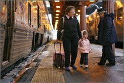 In this Feb. 20, 2007, file photo, Georgia Claussen, left, with her granddaughter Breanna Claussen, 3, of Grand Island, Neb., is thanked for traveling with Amtrak from Chicago by their train conductor Winifred Hane, right, in Washington. After half a century as more of a curiosity than a convenience, passenger trains are getting back on track in some parts of the country. (AP Photo/Jacquelyn Martin)