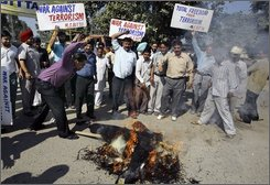Activists of the All India Anti-Terrorist Front shout slogans against Pakistan and the states' largest separatist group, the United Liberation Front of Asom as an activist beats a burning effigy symbolizing terrorism during a protest in Amritsar, India, Saturday, Nov. 1, 2008. Police arrested three people and are investigating whether local militants received help from other terrorist groups in carrying out coordinated attacks that killed at least 77 people in India's troubled northeast, officials said Saturday. (AP Photo/Altaf Qadri)