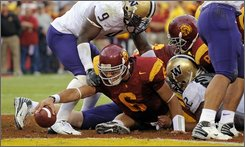 Southern California quarterback Mark Sanchez (6) scores a touchdown as Washington linebacker Donald Butler, top, defends during the first half of their NCAA college football game, Saturday, Nov. 1, 2008 in Los Angeles. (AP Photo/Mark J. Terrill)