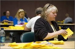 Boeing Machinists union member Carole Johnson of Issaquah, Washl., sorts through ballots after union members voted on a new contract offered by the company at the International Association of Machinists union hall in Seattle, Saturday Nov. 1, 2008. By 74% union members voted to accept the offer ending a 57-day strike. The workers are expected to return to Boeing's commercial airplane factories, which have been closed since the Sept. 6 walkout, starting Sunday night. (AP Photo/Stephen Brashear)