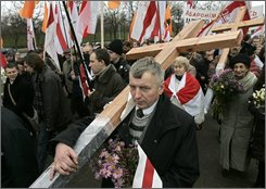Opposition activists carry wooden crosses and flags as they walk to the Kuropaty mass grave site of Soviet-era mass executions in the Belarus capital Minsk, Sunday, Nov. 2, 2008, to commemorate victims of Soviet-era political repression. Belarus' united opposition prefer the colors of the nation's post-Soviet flag, which Belarusian President Alexander Lukashenko replaced with an old Soviet one after his first election. (AP Photo/Sergei Grits)