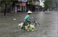 A vegetable seller goes through a flooded street in Hanoi,Vietnam, Sunday, Nov. 2, 2008.  Much of Vietnam's capital remained under water Sunday as the death toll from the city's worst flooding in two decades climbed to 17, disaster officials and state media reported.(AP Photo/Chitose Suzuki)