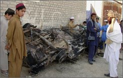 A Pakistani tribesman examines the wreckage of a car was hit by a suspected U.S. missile in Mir Ali village near Miran Shah, the main town of Pakistan's North Waziristan tribal region along Afghanistan border, Saturday, Nov. 1, 2008.  Suspected U.S. missiles slammed into two villages close to the Afghan border, killing at least 27 people including an Arab al-Qaida operative and other foreign militants, intelligence officials said.  (AP Photo/Hasbunallah Khan)