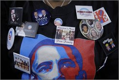 In this Oct. 27, 2008 file photo, a supporter wears buttons and a shirt as Democratic presidential candidate Sen. Barack Obama, D-Ill., speaks at a rally at the Mellon Arena in Pittsburgh. (AP Photo/Jae C. Hong, File)