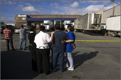 Gerardo Juarez, second right, and his wife Karen Solano, right, stand outside at a crime scene at a vegetable warehouse where Juarez's two brothers were found shot to death in Tijuana, Mexico, Monday, Nov. 3, 2008.  Juarez worked with his two brothers, Adolfo and Otilio, as a security guard at the warehouse where state police reported finding six bullet-ridden bodies and over 100 shell casings from assault rifles. (AP Photo/Guillermo Arias)