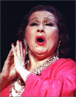 In this Sept. 25, 1989 file photo, singer Yma Sumac is shown performing in Boston.  Sumac, the Peruvian-born soprano who wowed international audiences in the 1950s with her stunning vocal range and modern take on South American folk music, died Saturday, Nov. 1, 2008, at an assisted-living home in Los Angeles after an eight-month bout with colon cancer, according to Sumac's friend and personal assistant Damon Devine. (AP Photo/Steven Senne, file)