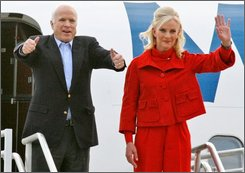 Republican presidential candidate Sen. John McCain, R-Ariz., left, accompanied by his wife Cindy, gestures as they arrive for a rally in a hanger at Pittsburgh International Airport in Moon Township, Pa., Monday, Nov. 3, 2008. (AP Photo/Gene J. Puskar)