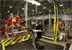 In this Sept. 12, 2008 file photo, James Ross works the assembly line making Chrysler's new 2009 Dodge Ram pickup at the Warren Truck Plant in Warren, Mich. The government said Tuesday, Nov. 4, 2008, factory orders dropped for the second straight month in September as businesses cut back on purchases of steel, computers and other equipment amid the economic downturn. (AP Photo/Carlos Osorio, file)