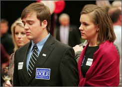 Meredith Jones, right, holds Mevin McGee as they listen to Sen. Elizabeth Dole, R-N.C., concession speech  on television  during the North Carolina Republican Election Party at the North Raleigh Hilton in Raleigh, N.C., Tuesday, Nov. 4, 2008. (AP Photo/Jim R. Bounds)